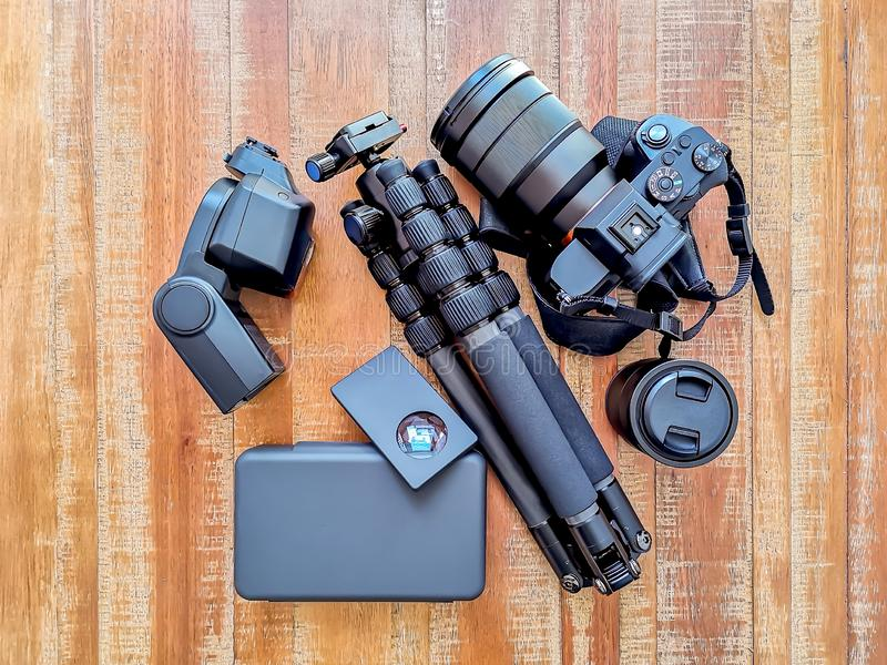 Photography Gear, Camera, tripod, flash and lenses at a wooden background stock photography
