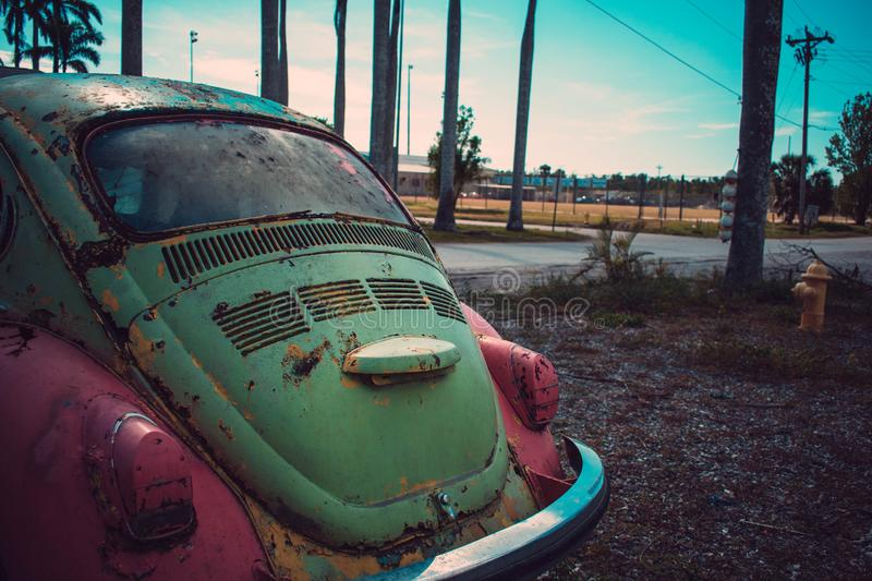 Photography of Green and Pink Volkswagen Beetle Parked Beside The Road royalty free stock photo