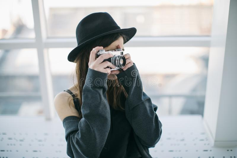 Photography hobby. Stylish ypung photographer girl in black hat. Soft backlight stock photography