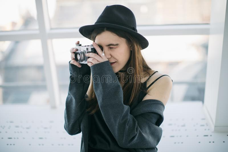 Photography hobby. Stylish ypung photographer girl in black hat. Soft backlight. Side view stock photos