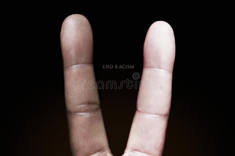 Photography idea showing a black and white finger making a peace sign against racism. Photograph of two fingers making a peace sign on a black background stock images