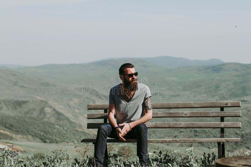 Photography of a Man Sitting on Wooden Bench stock photo