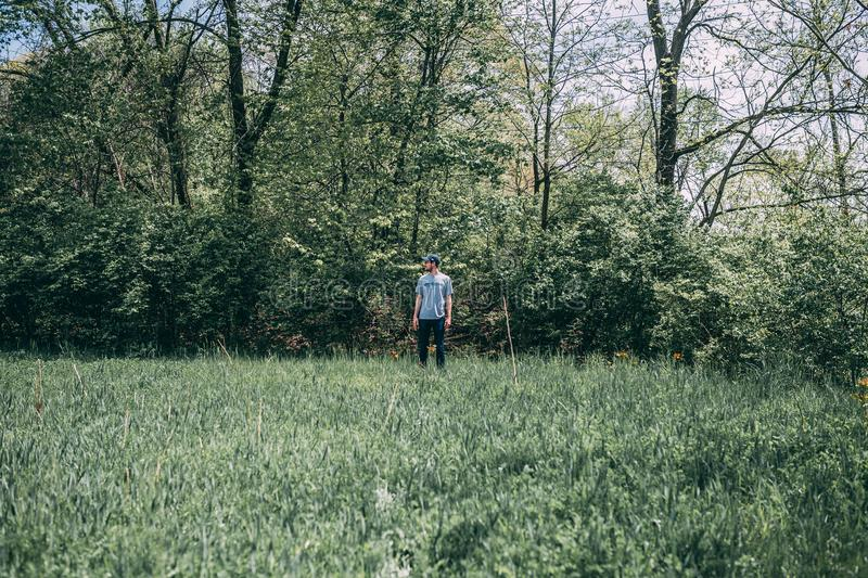 Photography of a Man Standing on Grass Field royalty free stock images