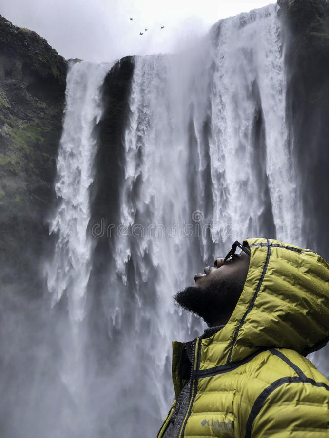 Photography of Man Wearing Bubble Hoodie Jacket Near Waterfalls royalty free stock image