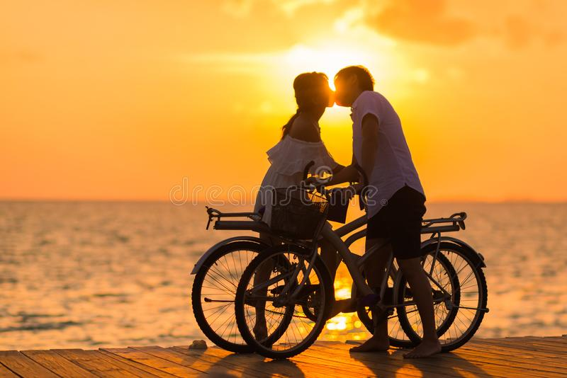 Photography of Man Wearing White T-shirt Kissing a Woman While Holding Bicycle on River Dock during Sunset royalty free stock image