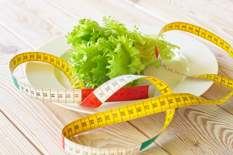 Photography of measuring tape on white plate with green salad leaves. Dieting concept image royalty free stock photos