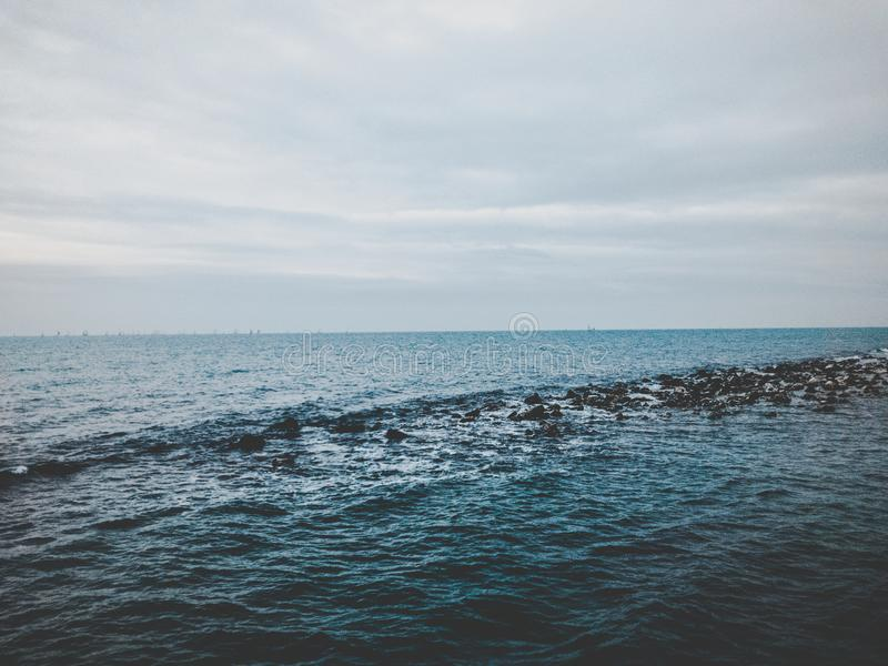 Photography of Ocean Under Cloudy Sky stock photography