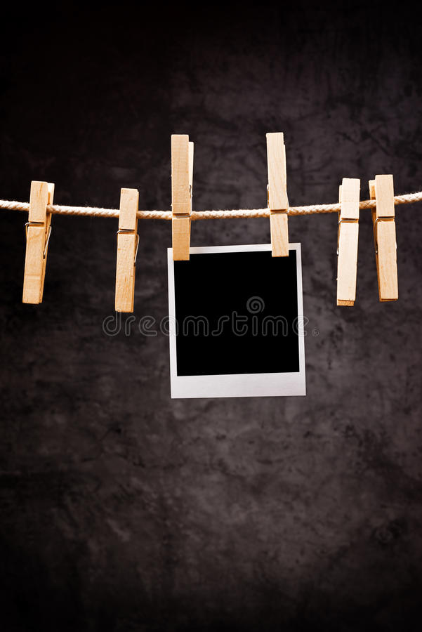 Photography paper with instant photo frame attached to rope with. Clothes pins. Copy space for your image royalty free stock photography
