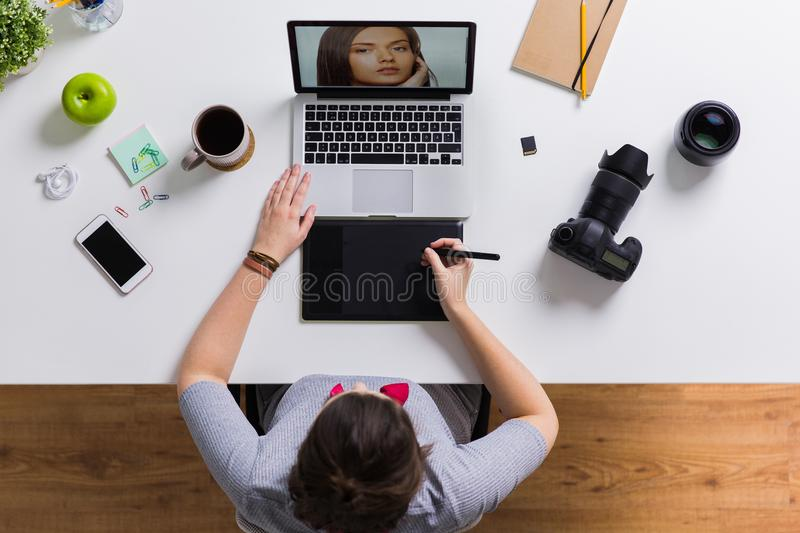 Woman with camera working on laptop at table. Photography, people and design concept - hands with graphic tablet retouching photo on laptop computer and camera royalty free stock image