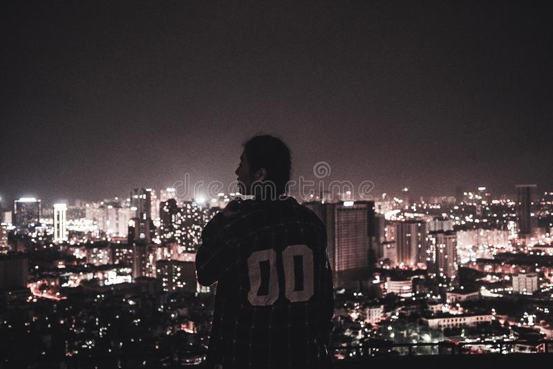 Photography of a Person Watching over City Lights during Night Time royalty free stock image