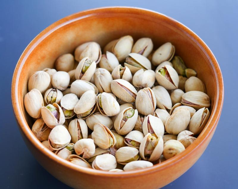Pistachios in shell on a bowl. Photography of salted and roasted pistachios in shell on a bowl. The photography has been taken on a blue background royalty free stock image