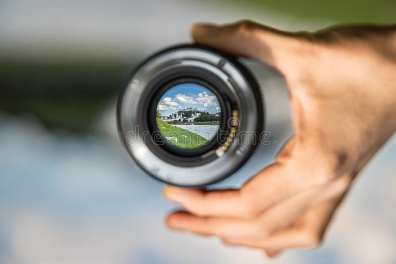 Photography in Salzburg: Hand holding camera lens with old city of Salzburg. Hand holding camera lens with old city of Salzburg in it, close up royalty free stock images