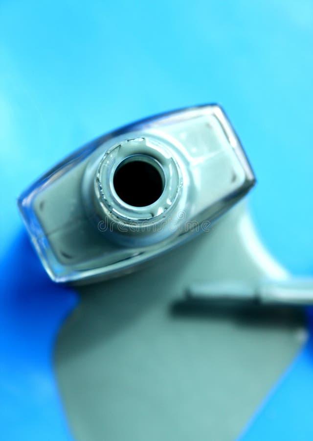 Photography of spilled nail polish enamel light green bottle on blue background royalty free stock images