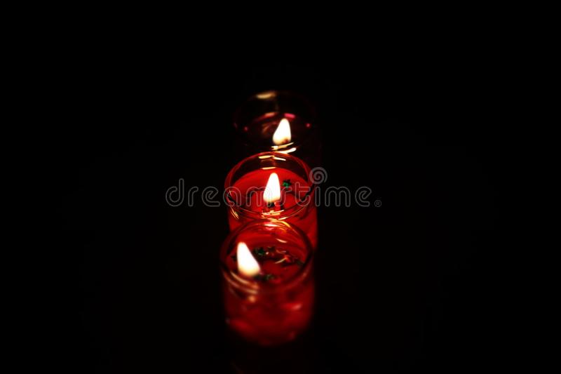 Photography Three Tealight Candles in Dark Place stock photography
