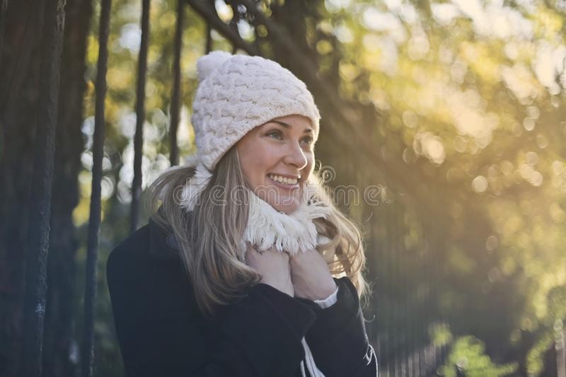 Photography of Woman in Black Jacket and White Knit Cap Smiling Next to Black Metal Fence stock image