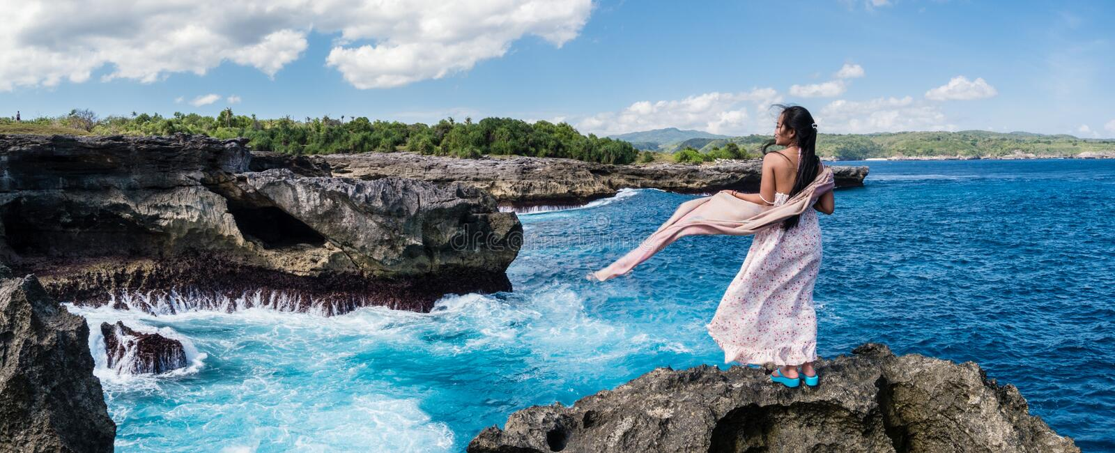 Photography of Woman Standing on Rock in Front of Sea stock image