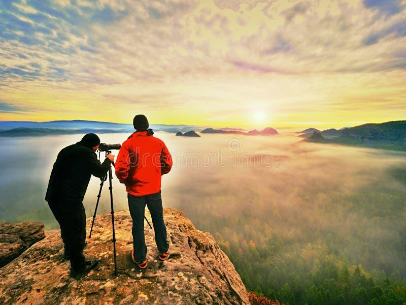 Photographying en naturaleza salvaje Fotógrafo de la naturaleza con la cámara grande en estancia del trípode en roca de la cumbre fotografía de archivo libre de regalías