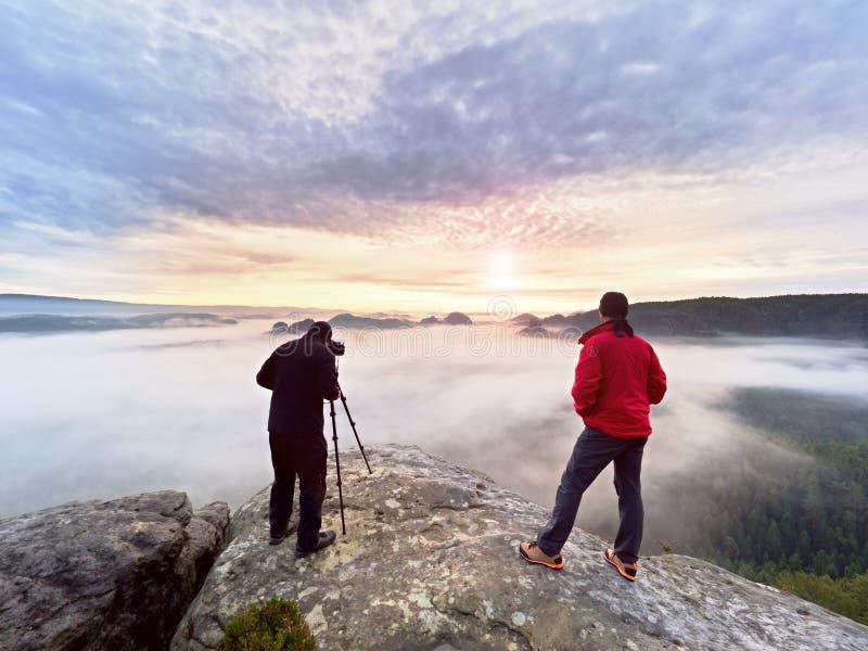 Photographying en naturaleza salvaje Fotógrafo de la naturaleza con la cámara grande en estancia del trípode en roca de la cumbre fotos de archivo libres de regalías