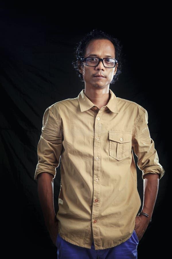 Photogrpahy med studioljus av den asiatiska mannen som bär brun skjorta a royaltyfri foto