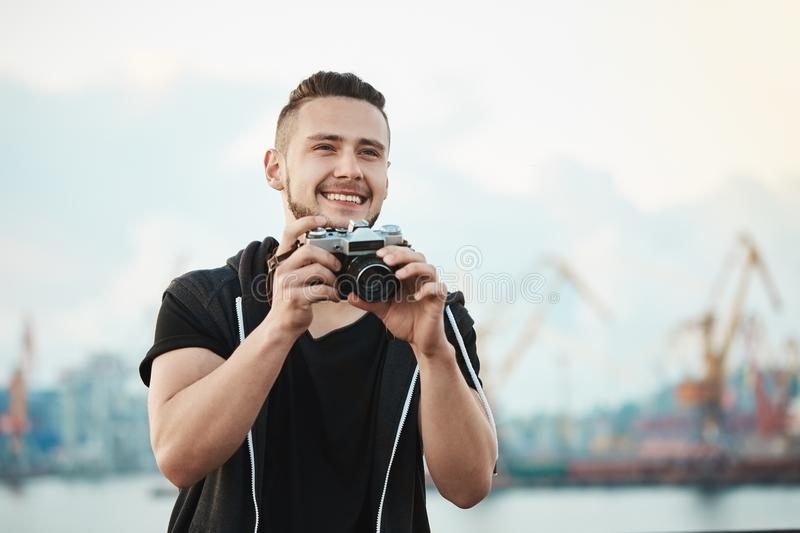 Photojournalist likes his work. Portrait of happy pleased handsome photographer smiling broadly while looking aside and royalty free stock photos
