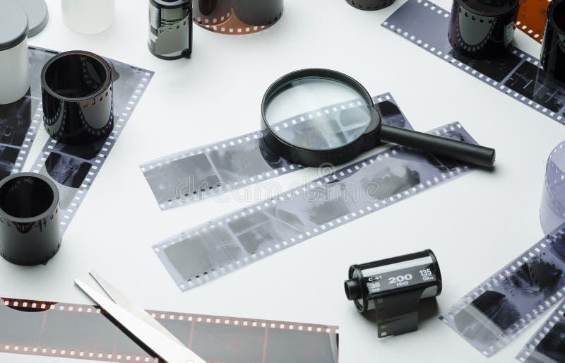 Photonegatives, bobines de film de 35mm et loupe sur le fond blanc images libres de droits