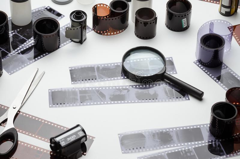 Photonegatives, 35 mm film, magnifying glass and scissors. On white background royalty free stock photos