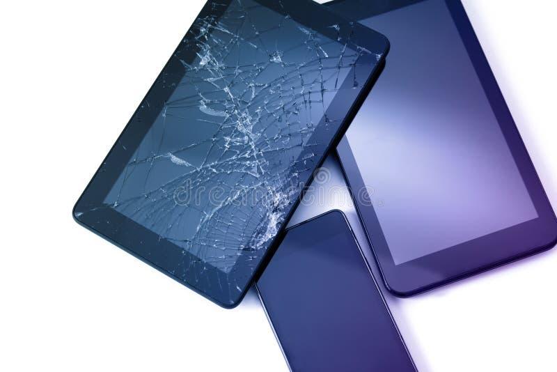 Photos d'un écran fissuré sur une tablette et un téléphone portable noir isolés en blanc Tablette avec écran endommagé photos stock