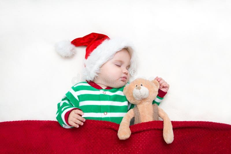 Photos de jeune bébé dans un chapeau de Santa Claus images stock