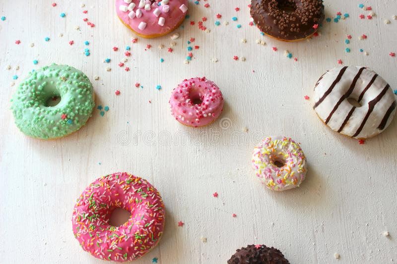Assorted colorful donuts close-up. Photos of different donuts. Assorted colorful donuts in pink, green, chocolate icing close-up, sweet dessert royalty free stock photography
