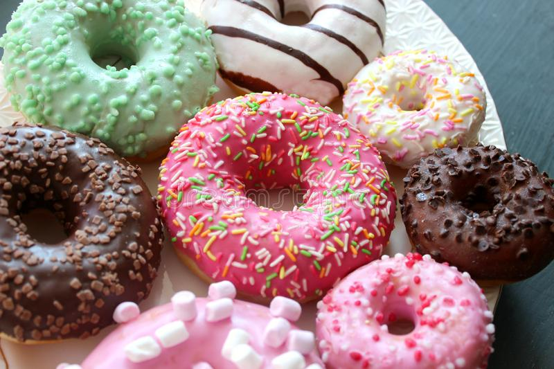 Assorted colorful donuts close-up. Photos of different donuts. Assorted colorful donuts in pink, green, chocolate icing close-up, sweet dessert stock photography