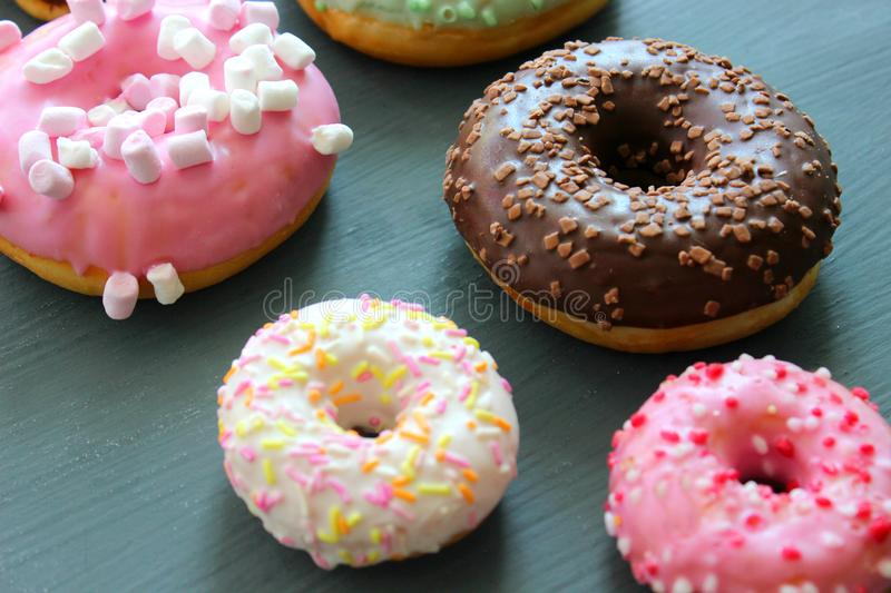 Photos of different donuts, free space for writing texts. Photos of different donuts. Assorted colorful donuts in glaze close-up, free space for writing texts royalty free stock images