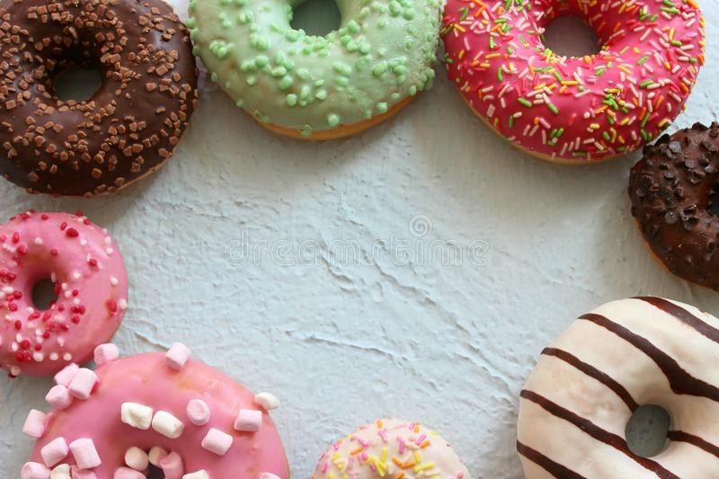 Photos of different donuts, free space for writing texts. Photos of different donuts. Assorted colorful donuts in glaze close-up, free space for writing textsn stock photos