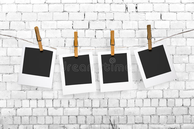 Photos hanging on a clothesline on brick wall background stock illustration