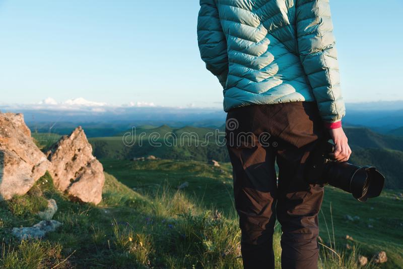 Photos on the shoulders behind the girl photographer in nature with a camera in hand. Back view royalty free stock images
