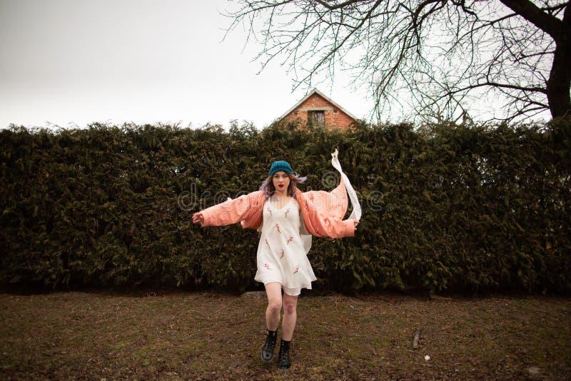 Photosession красивой девушки в белом платье на предпосылке загородки елей стоковая фотография rf