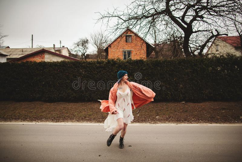 Photosession красивой девушки в белом платье на предпосылке загородки елей стоковое изображение