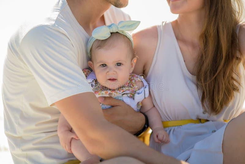 Photosession actif heureux de famille belle mère aux cheveux longs son mari avec son repos d'enfant en parc d'atraction photographie stock