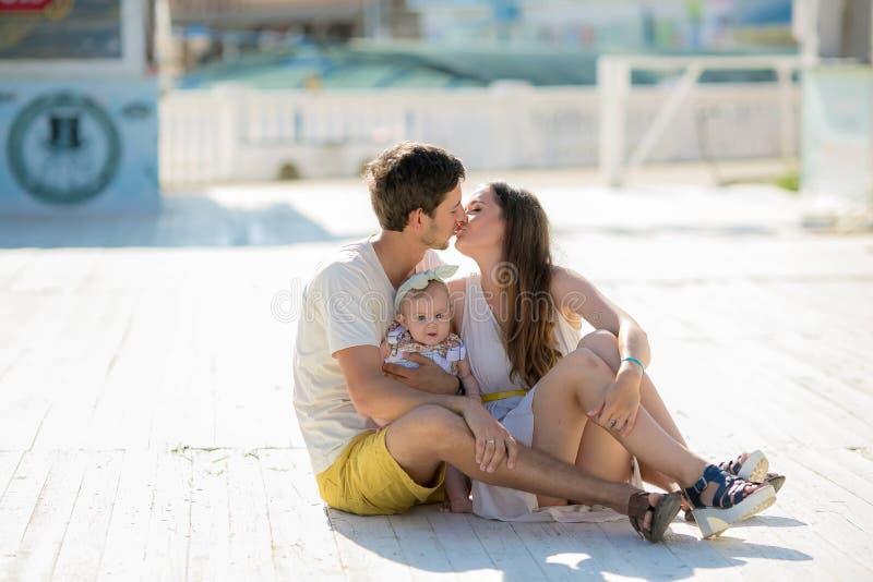 Photosession attivo felice della famiglia bella madre dai capelli lunghi il suo marito con il suo resto del bambino nel parco di  fotografia stock
