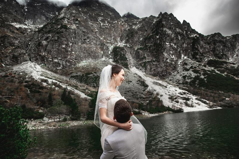 Photosession bonito do casamento O noivo circunda sua noiva nova, na costa do lago Morskie Oko poland fotografia de stock