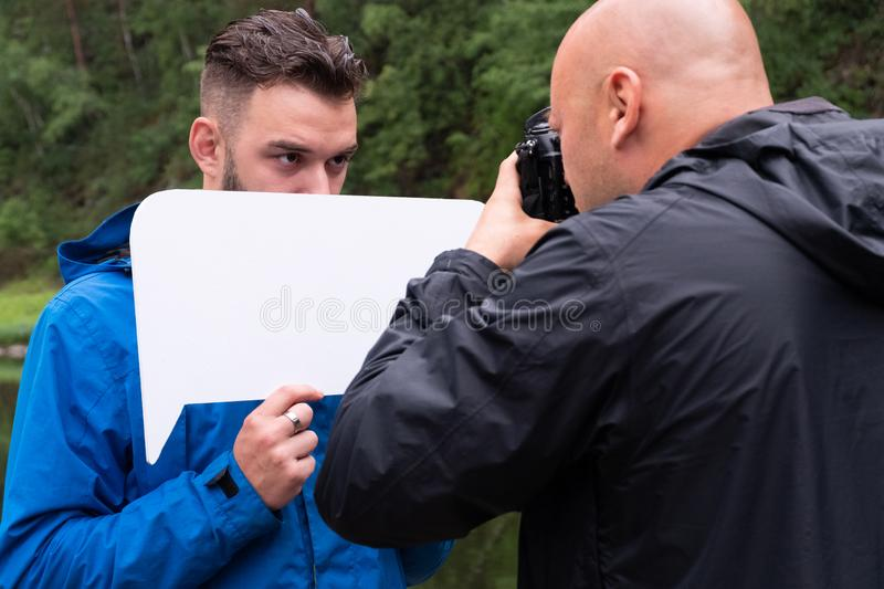 Bald photographer works with a model guy. Photosession in nature. A young man hides his face behind a white sign. stock photo