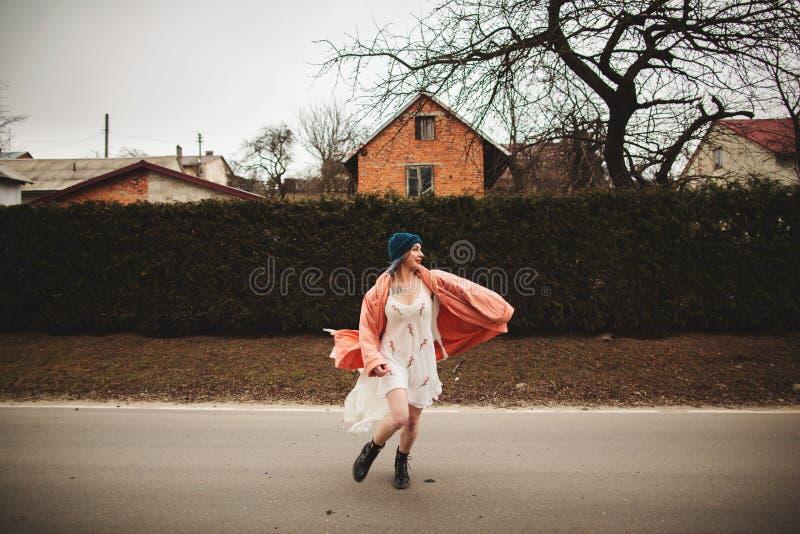 Photosession van een mooi meisje in een witte kleding op de achtergrond van sparren schermt stock afbeelding