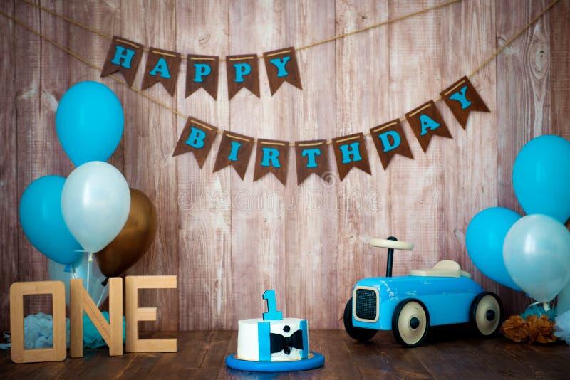 Photoshoot一个小男孩绅士的易碎smashcake 与一辆木减速火箭的汽车和氦气气球的装饰的photozone 愉快 图库摄影