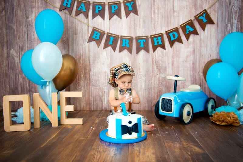 Photoshoot一个小男孩绅士的易碎smashcake 与一辆木减速火箭的汽车和氦气气球的装饰的photozone 愉快 库存照片