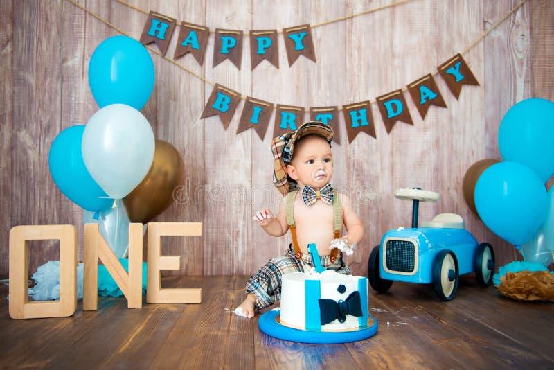 Photoshoot一个小男孩绅士的易碎smashcake 与一辆木减速火箭的汽车和氦气气球的装饰的photozone 愉快 库存图片
