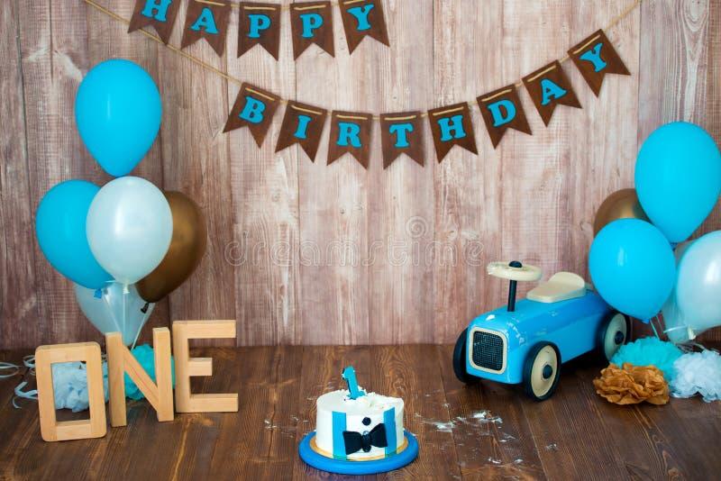 Photoshoot一个小男孩绅士的易碎smashcake 与一辆木减速火箭的汽车和氦气气球的装饰的photozone 愉快 免版税库存照片