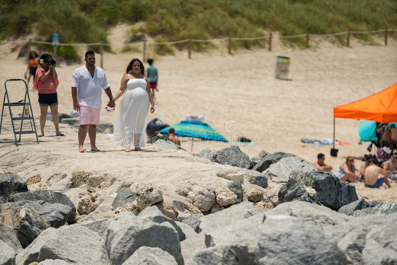 Photoshoot, das im Miami Beach geschieht Weiblicher Fotograf, der ein Paar im Weiß schießt stockbild