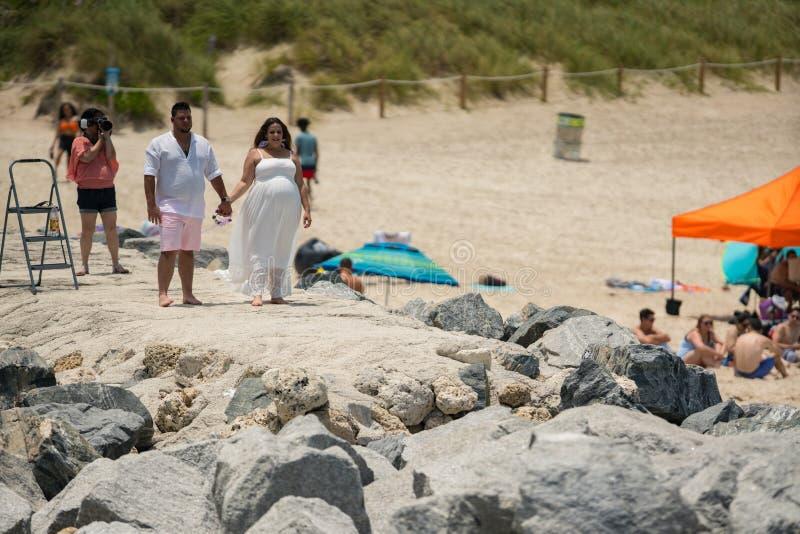 Photoshoot, das im Miami Beach geschieht Weiblicher Fotograf, der ein Paar im Weiß schießt stockbilder