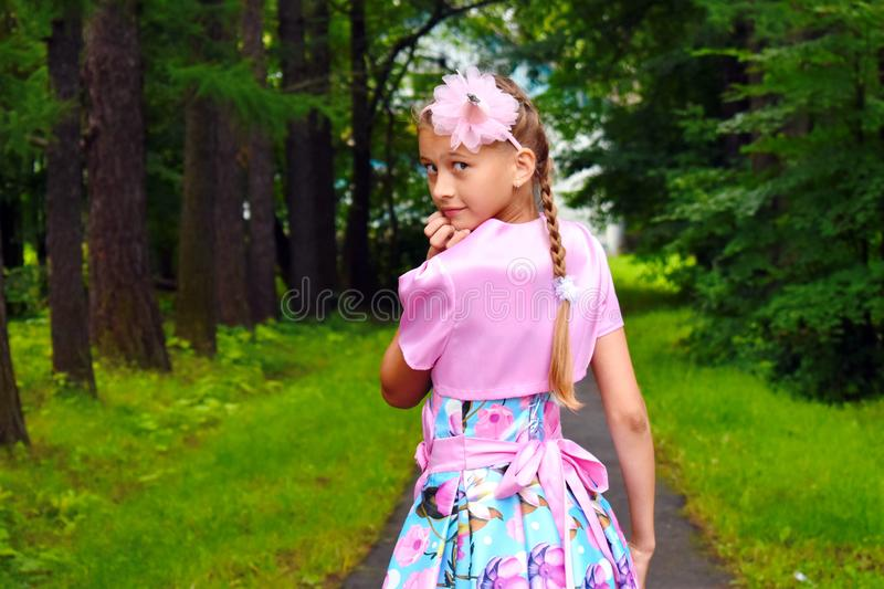 Girl in a beautiful pink ball dress in forest. Girl the princess fairy in a garden in the summer stock images