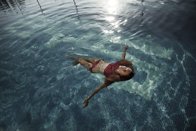 Photoshoot in het zwembadhoogtepunt van duidelijk blauw water met gebronst mooi model dat het ontspannen is, genietend van de aar stock foto's