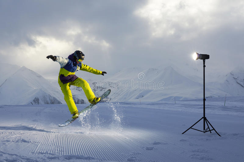 Photoshoot snowboarder who jumps. artificial light from flash royalty free stock image
